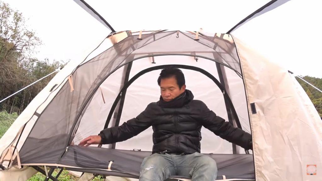 タンスのゲンのコット用テントをレビューする尾上祐一郎さん